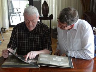 Dhr. Vroom en René Ros bladeren door het Duitse fotoalbum over Nederlandse verdedigingswerken.