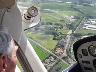 Piloot in cockpit boven Uithoorn.